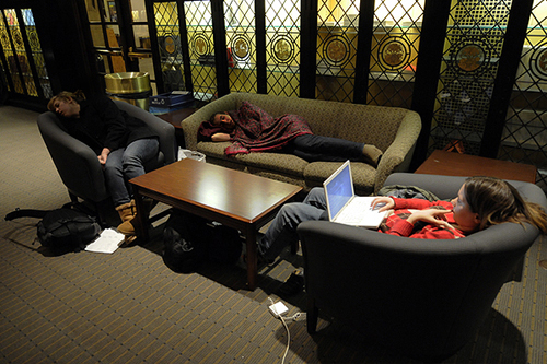 Two students sneak in a nap while a third studies for a final around 5:10 p.m. Monday in the McCormick Tribune Lounge in Hutchinson Commons.